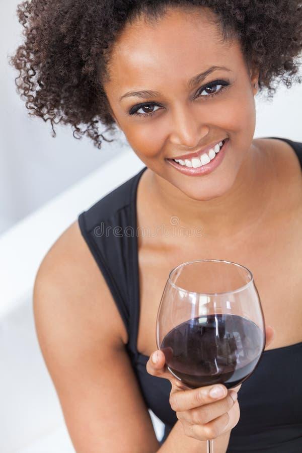 Muchacha del afroamericano de la raza mixta que bebe el vino rojo foto de archivo libre de regalías