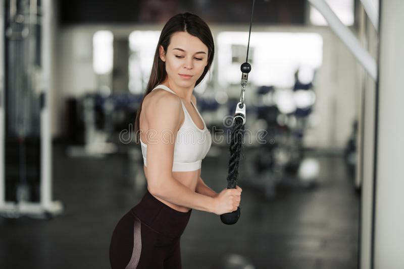 Muchacha del atleta en ropa de deportes que resuelve y que entrena a sus brazos y hombros con la m?quina del ejercicio en gimnasi foto de archivo libre de regalías