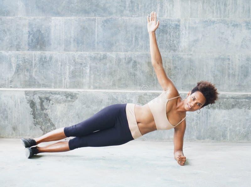 Muchacha del atleta del isleño pacífico con el afro que se realiza ejercitando el tablón de las rutinas con la torsión, una mano  fotografía de archivo libre de regalías