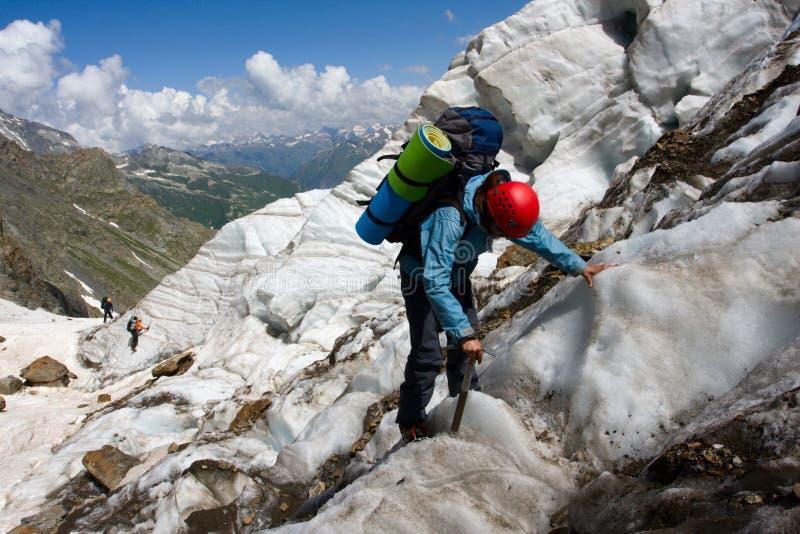 Muchacha del Backpacker con el hielo-hacha imagen de archivo