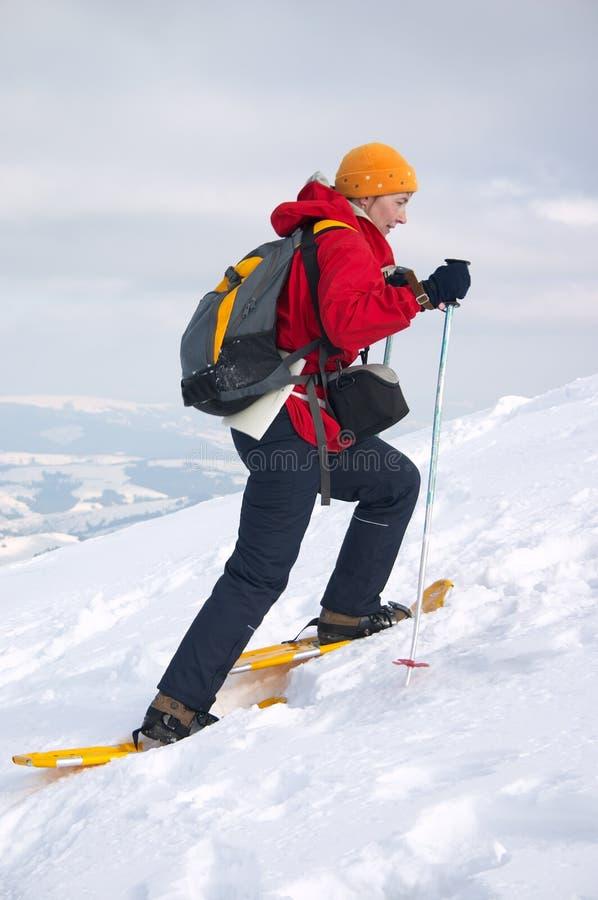 Muchacha del Backpacker en zapatos de la nieve fotografía de archivo
