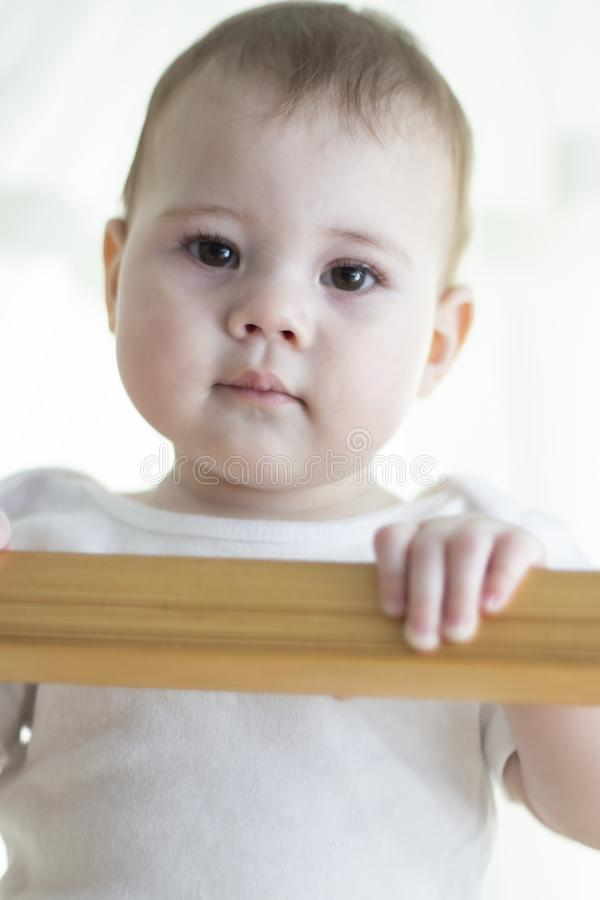 Muchacha del bebé con las miradas blancas fuera del pesebre abajo Retrato de un primer del niño Foco suave Ojos lindos del marrón fotografía de archivo
