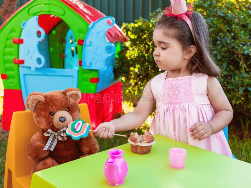 Muchacha del bebé que juega en la fiesta del té al aire libre que alimenta su bff Teddy Bear del mejor amigo con una piruleta sab imagen de archivo libre de regalías
