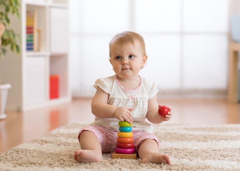 Muchacha del beb? que juega con los juguetes de madera y que se divierte foto de archivo libre de regalías