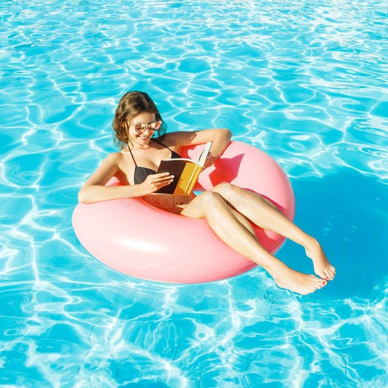 Muchacha del bikini con las gafas de sol relajadas y el libro de lectura en el anillo inflable rosado de la piscina fotos de archivo libres de regalías