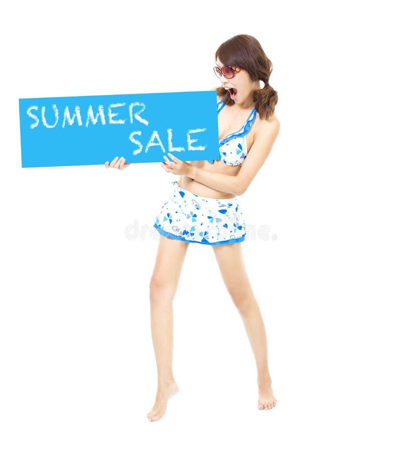 Muchacha del bikini que lleva a cabo una muestra de la venta del verano foto de archivo libre de regalías
