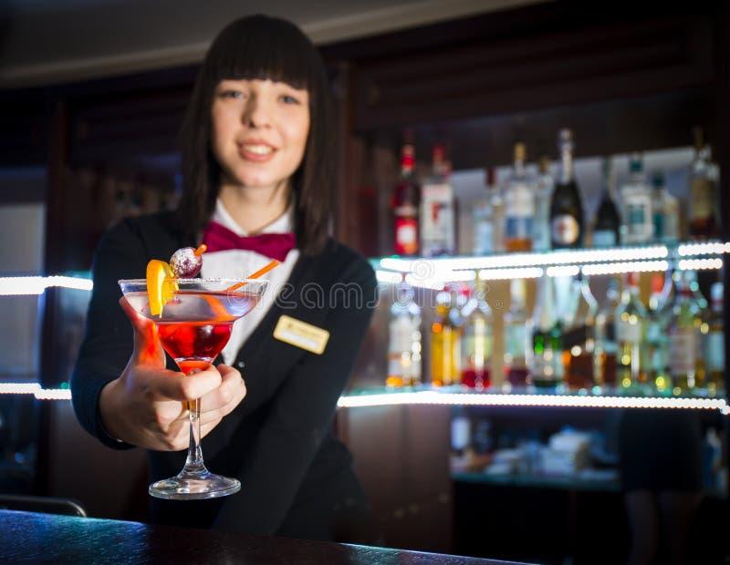 Muchacha del camarero en la camarera de ofrecimiento contraria del coctail del club de noche imagen de archivo