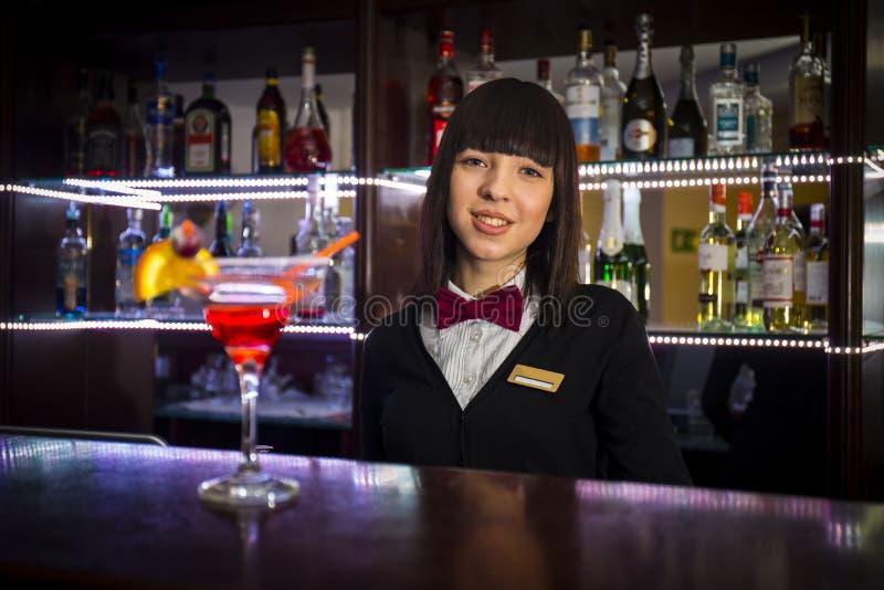 Muchacha del camarero en la camarera de ofrecimiento contraria del coctail del club de noche foto de archivo