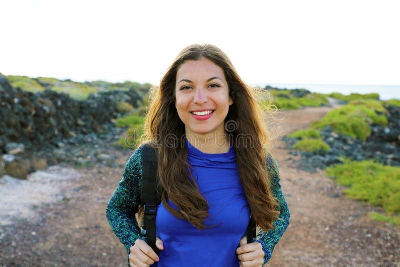 Muchacha del caminante con la mochila que camina en el norte de la isla de Lanzarote Mujer que camina joven que mira feliz la cám imagenes de archivo