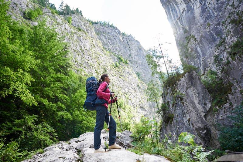 Muchacha del caminante que se coloca antes de pared enorme del acantilado imagen de archivo