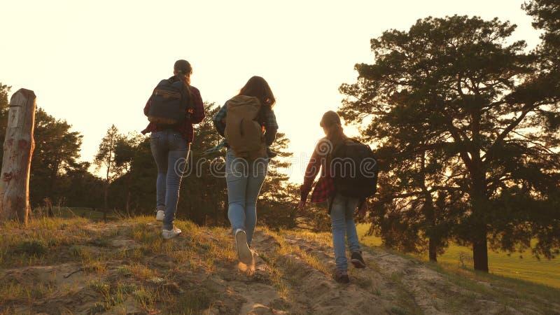 Muchacha del caminante tres muchachas viajan, caminan a través del bosque para subir la colina para disfrutar y para aumentar sus fotografía de archivo libre de regalías