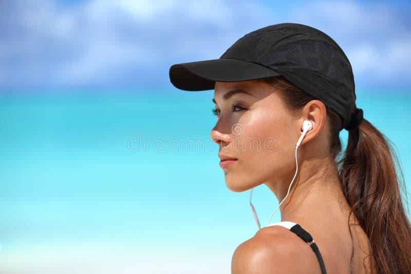 Muchacha del corredor de la aptitud que escucha la música en la playa imagen de archivo