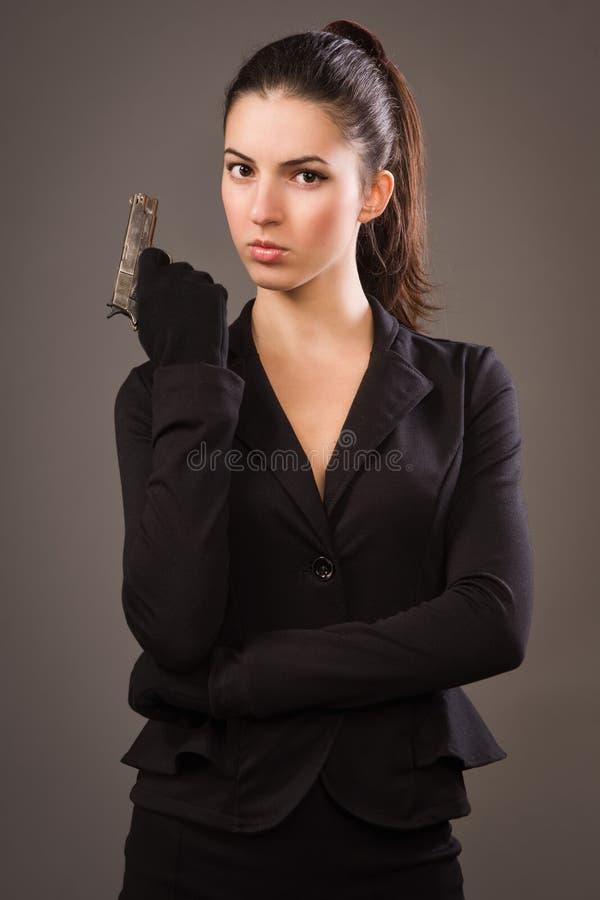 Muchacha del espía en un negro con el arma fotografía de archivo