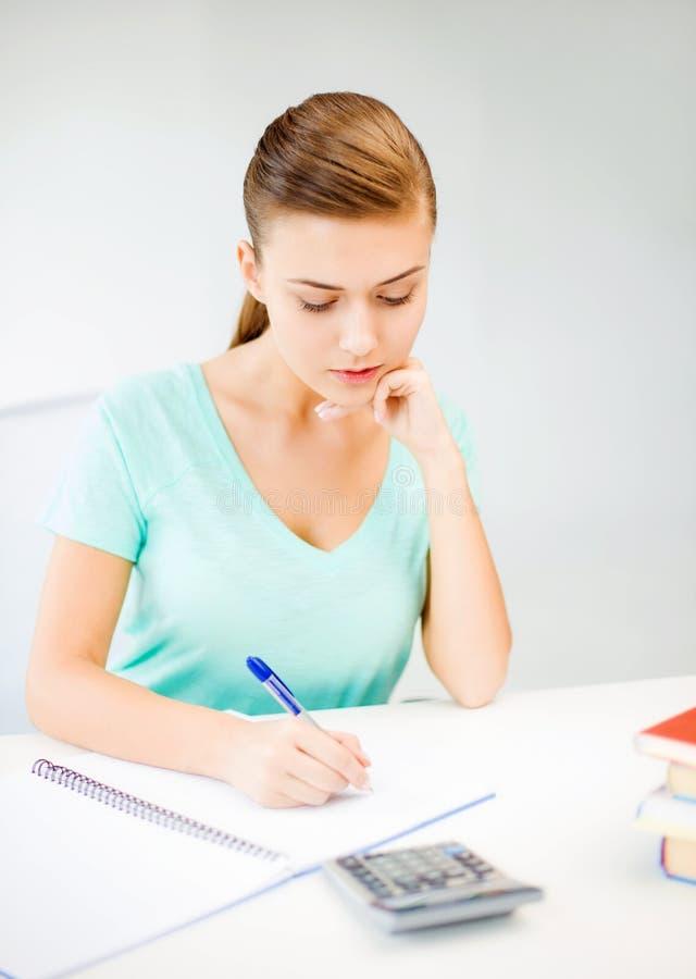 Muchacha del estudiante con el cuaderno y la calculadora foto de archivo