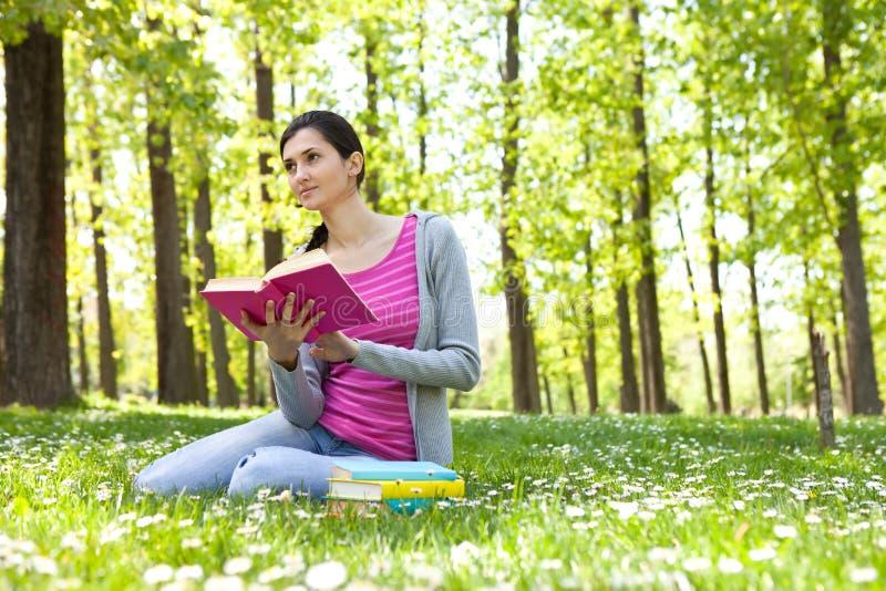 Muchacha del estudiante con el libro en hierba fotos de archivo