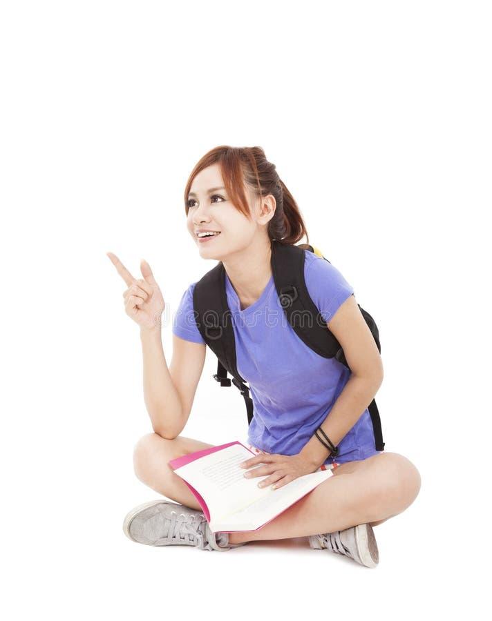 Muchacha del estudiante con el libro y el señalar en algo fotografía de archivo