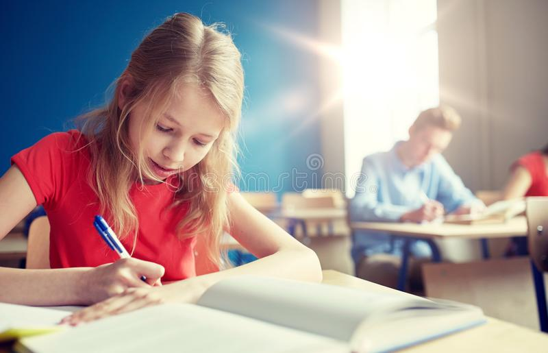 Muchacha del estudiante con la prueba de la escuela de la escritura del libro foto de archivo libre de regalías