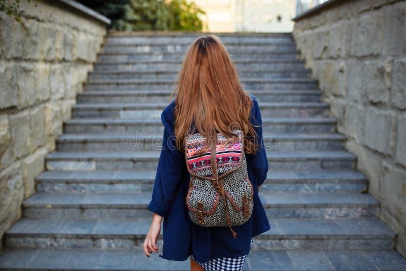 Muchacha del estudiante con las escaleras que suben de una mochila foto de archivo