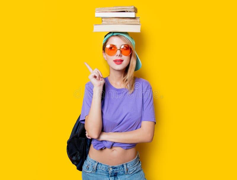 Muchacha del estudiante con los vidrios y los libros anaranjados imagenes de archivo