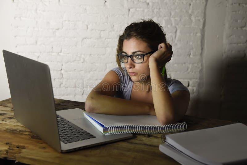 Muchacha del estudiante o trabajadora atractiva joven que se sienta en el escritorio del ordenador en la tensión que mira haber a foto de archivo