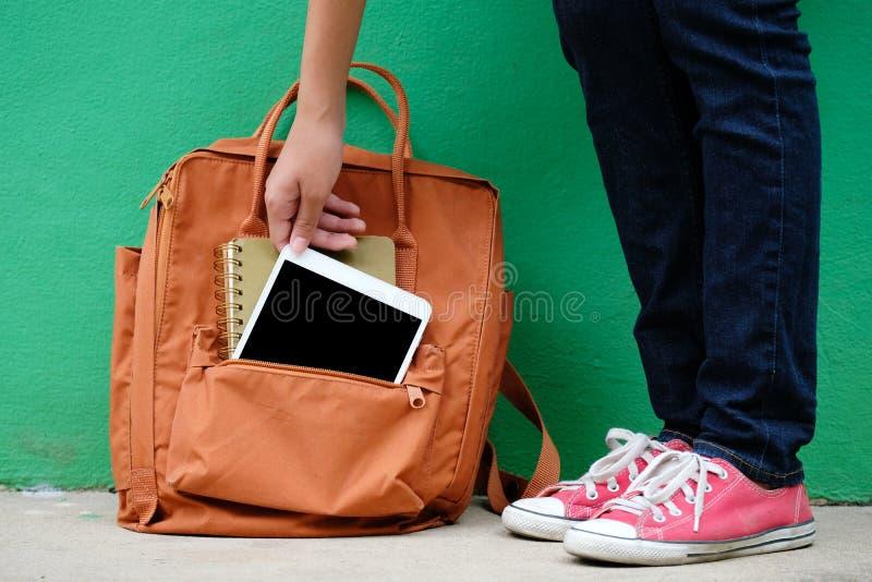 Muchacha del estudiante que sostiene la tableta digital del bolso de escuela, educ en línea fotos de archivo