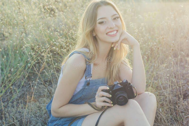 Muchacha del fotógrafo que hace imágenes por la cámara vieja foto de archivo libre de regalías
