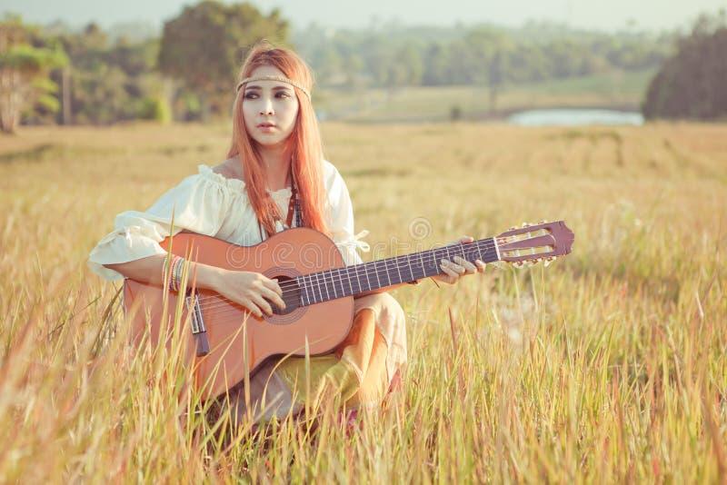 Muchacha del hippie que toca la guitarra en hierba imagen de archivo
