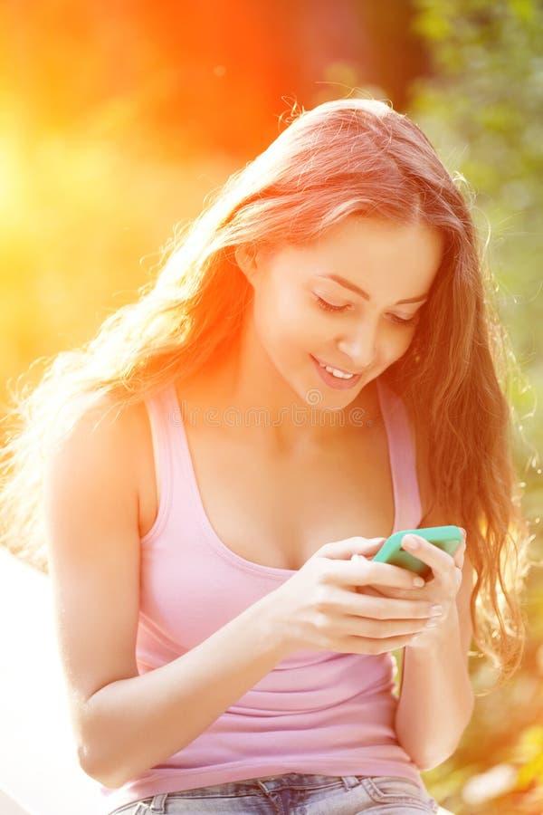 Muchacha del inconformista con un smartphone en el fondo de la puesta del sol Woma foto de archivo libre de regalías