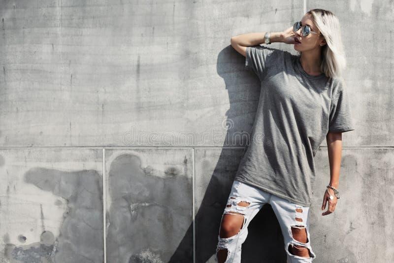 Muchacha del inconformista en camiseta gris sobre la pared de la calle fotografía de archivo