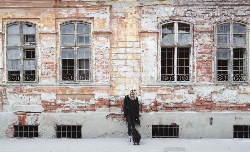Muchacha del inconformista en negro delante de la casa vieja de la ruina imagen de archivo