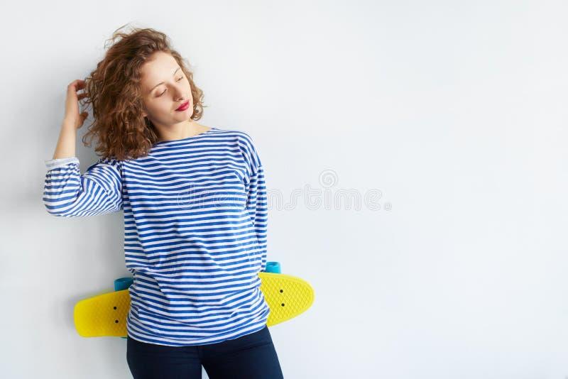 muchacha del inconformista que sostiene un monopatín aislado en blanco foto de archivo libre de regalías
