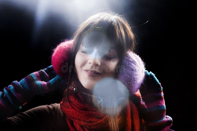 Muchacha del invierno con las orejeras y la llamarada fotografía de archivo libre de regalías