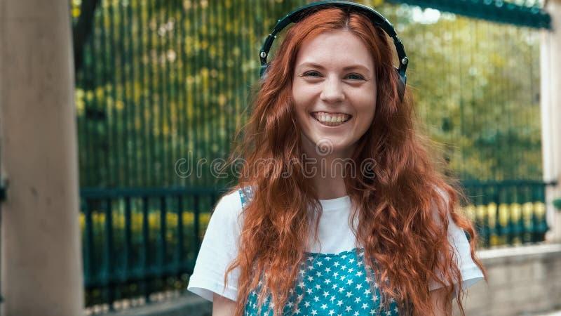 Muchacha del jengibre que escucha la música en auriculares grandes imagenes de archivo