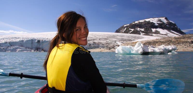 Muchacha del kajak en el lago del glaciar imagen de archivo