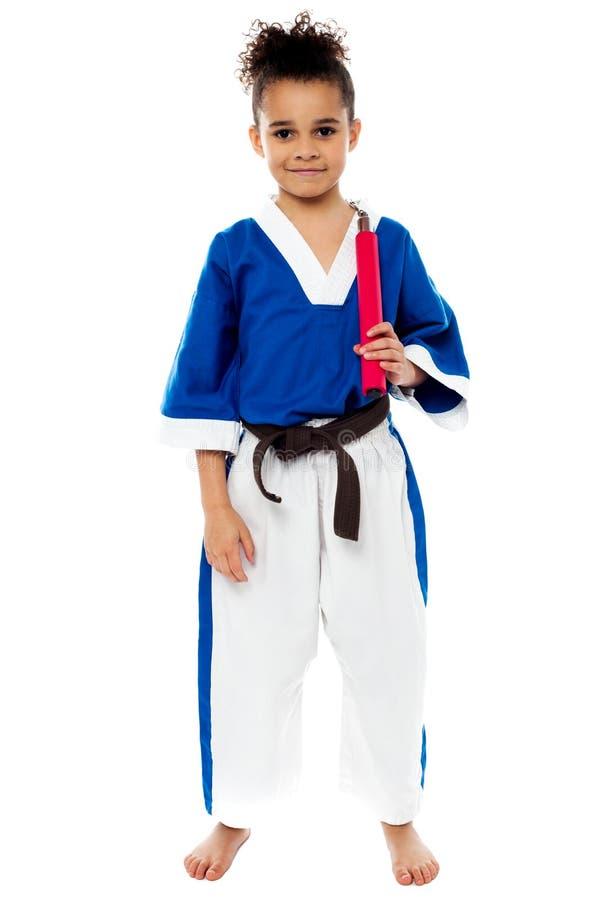 Muchacha del karate que lleva a cabo nunchucks fotos de archivo