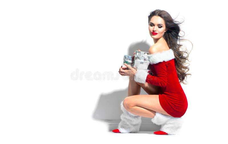 Muchacha del modelo de la belleza de la Navidad que lleva el vestido rojo de santa que sostiene los regalos Mujer joven morena at foto de archivo libre de regalías