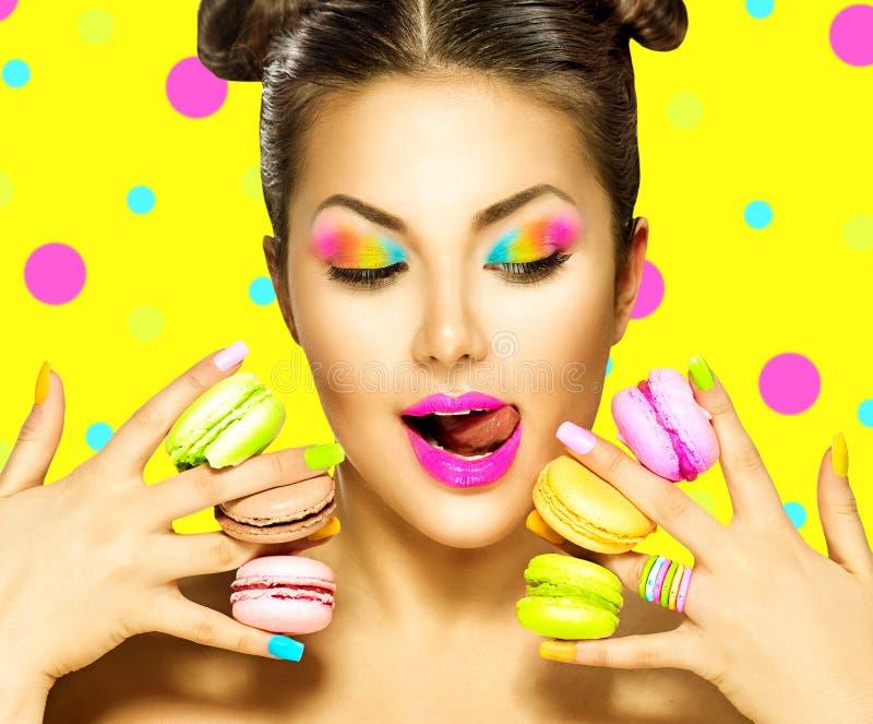 Muchacha del modelo de moda de la belleza que toma los macarrones coloridos foto de archivo