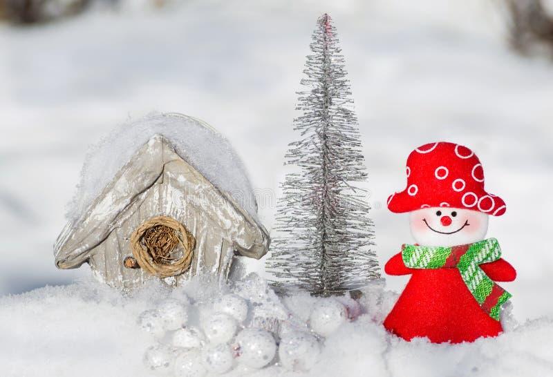 Muchacha del muñeco de nieve de la tarjeta de Navidad al lado de un árbol plateado y de una casa del pájaro, fotografía de archivo libre de regalías