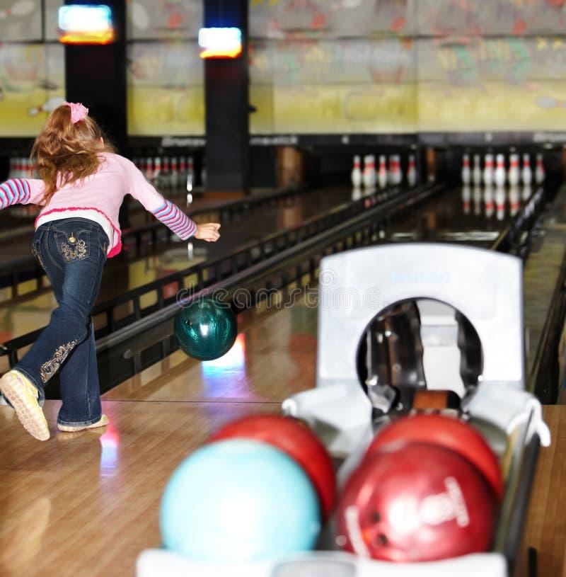 Muchacha del niño adentro con la bola de bowling. foto de archivo