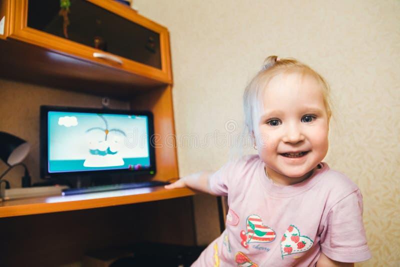 Muchacha del niño cerca del ordenador fotografía de archivo