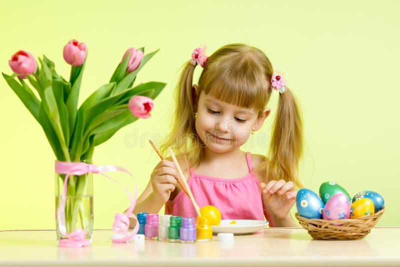 Muchacha del niño con el cepillo que colorea los huevos de Pascua imágenes de archivo libres de regalías