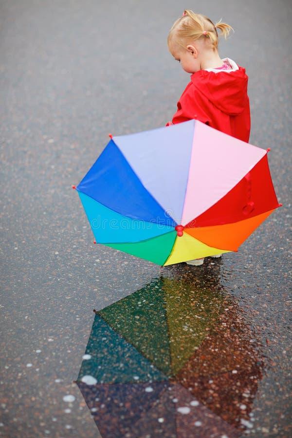 Muchacha del niño con el paraguas colorido en día lluvioso fotografía de archivo