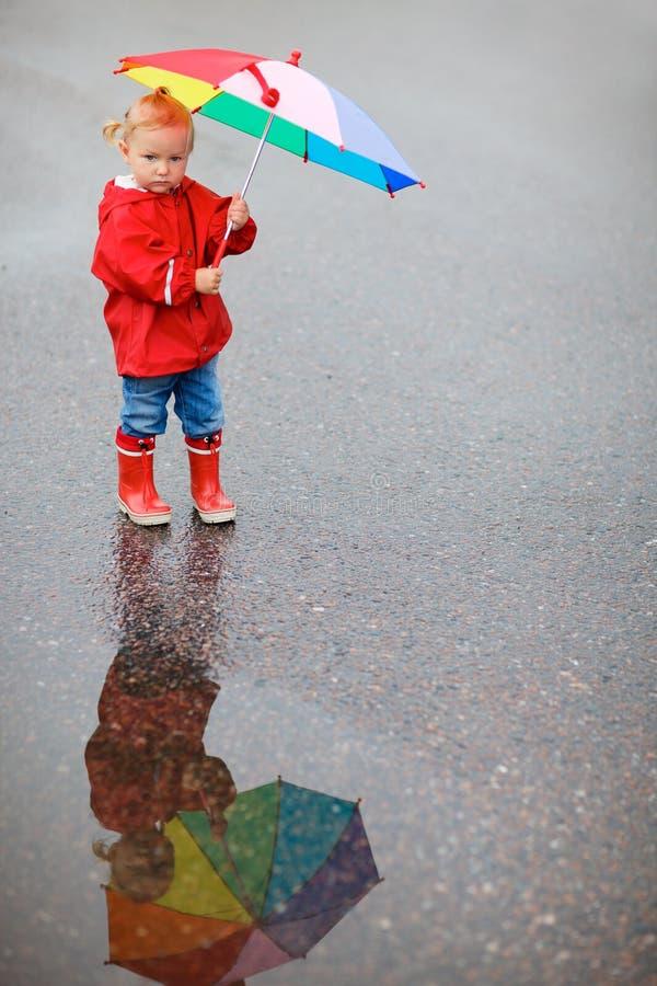 Muchacha del niño con el paraguas colorido en día lluvioso imagen de archivo