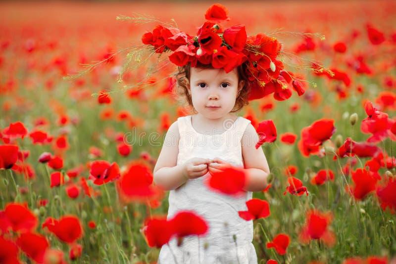 Muchacha del niño con el ramo de amapolas foto de archivo libre de regalías