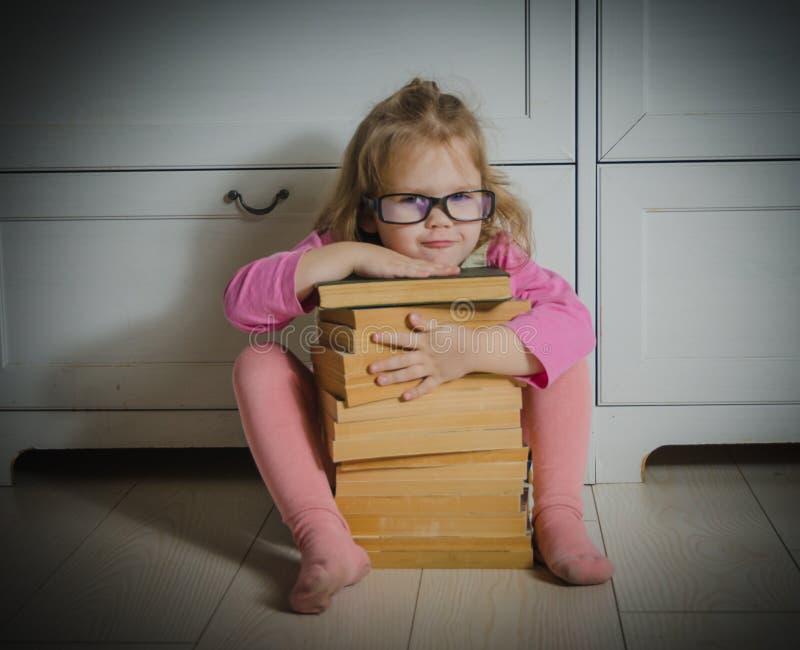 Muchacha del niño con los vidrios y una pila de libros que se sientan en el piso imagenes de archivo