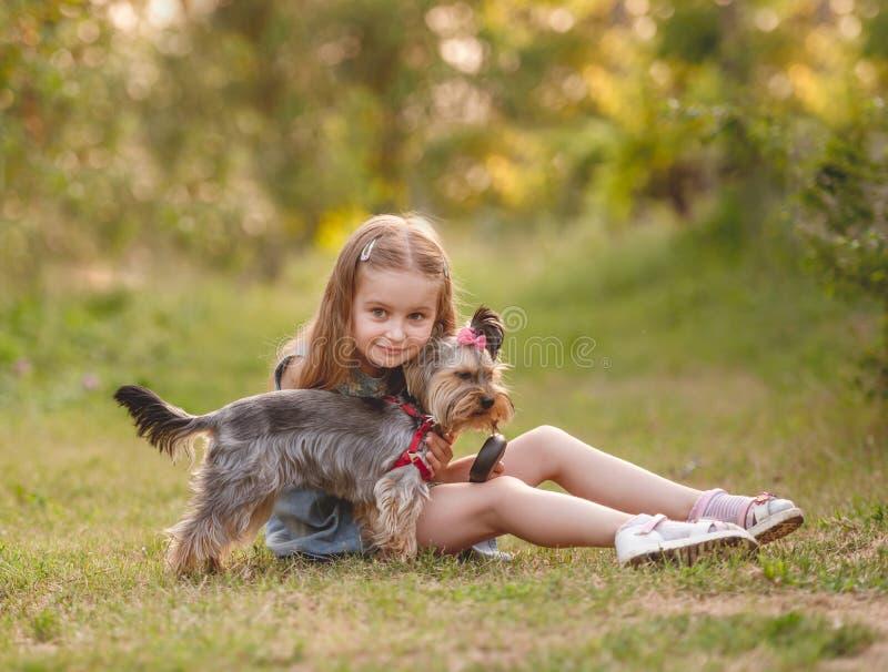Muchacha del niño con su pequeño perro del terrier de Yorkshire en el parque fotos de archivo libres de regalías