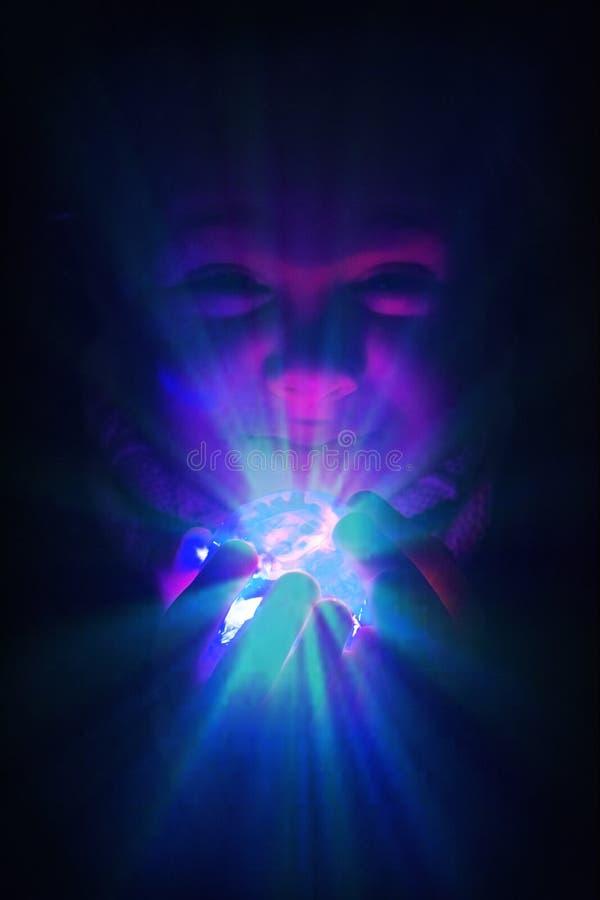 Muchacha del niño con una bola de cristal brillante con la llamarada luces Metáfora de la imaginación y de la fantasía con el esp imagenes de archivo