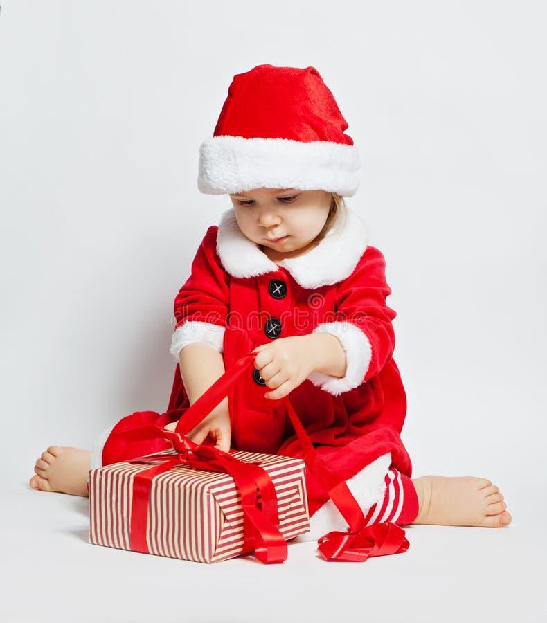 Muchacha del niño de la Navidad en el sombrero de Papá Noel que abre la caja de regalo de Navidad foto de archivo