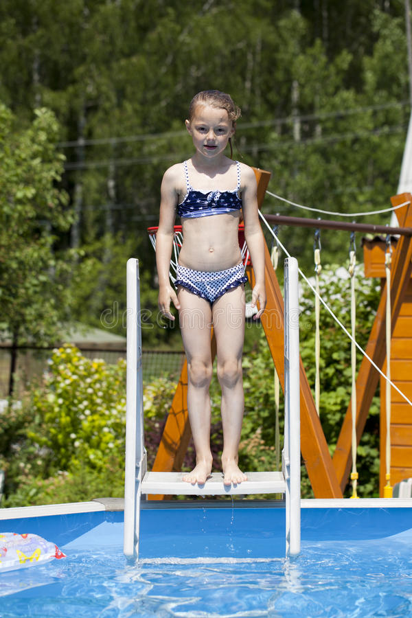 Muchacha del niño en bikini azul cerca de la piscina Verano caliente fotos de archivo