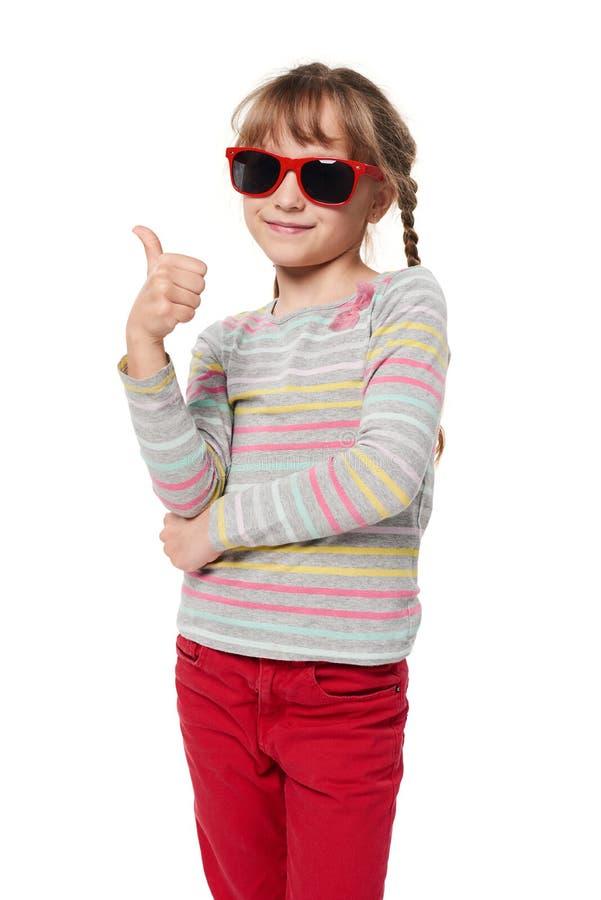 Muchacha del niño en gafas de sol que gesticula el pulgar para arriba imagen de archivo